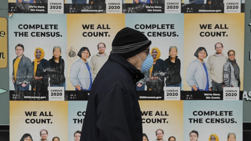 A person wearing a mask walks past posters encouraging participation in the 2020 census in April in Seattle.