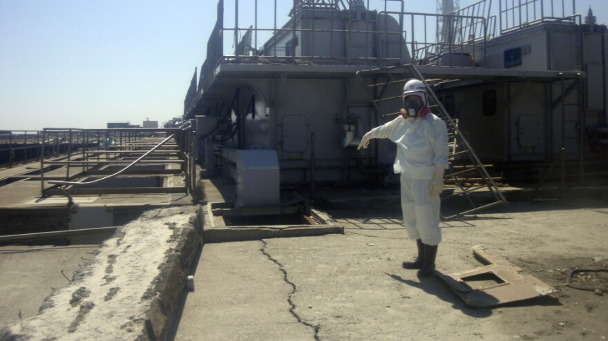 A TEPCO employee points at a crack discovered April 1 in a maintenance pit on the edge of the Fukushima Dai-ichi nuclear nuclear power plant in northeastern Japan.