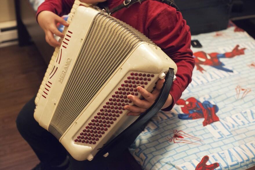 """Alex, de 14 años de edad, toca el acordeón en su cuarto. Se está aprendiendo la canción """"<em>La Puerta Negra</em>"""" , una de las canciones favoritas de su padre. Su rendimiento escolar decayó mucho durante el período de detención de Manuel."""