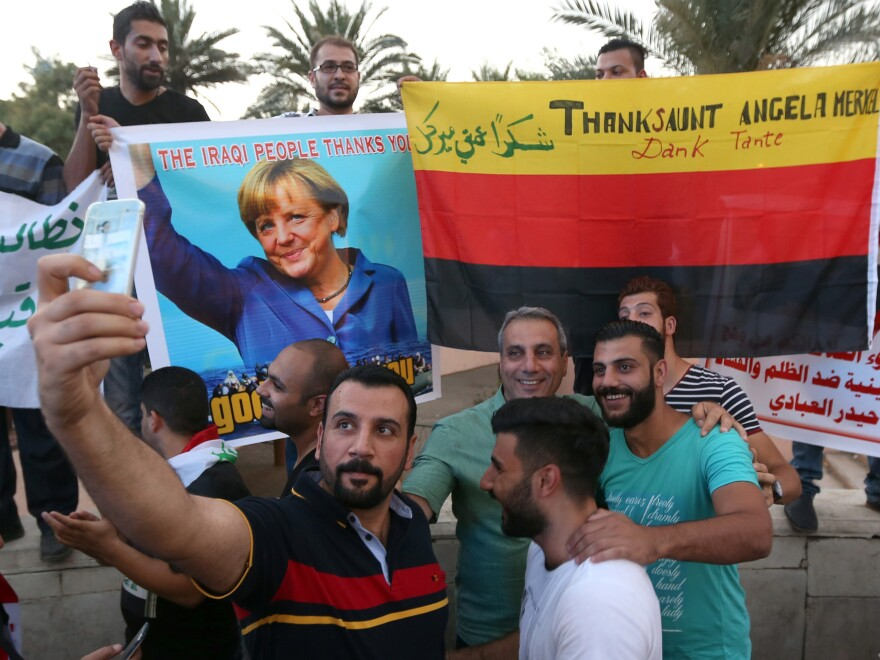 Iraqi protesters hold a picture of German Chancellor Angela Merkel during a demonstration calling for government reforms on Friday. Thousands of Iraqis are leaving the country, fleeing violence and a dire economy and drawn toward the perception of a welcoming Europe.