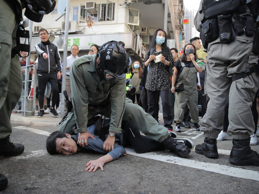 A protester is detained in Hong Kong on Monday. Hong Kong is in the sixth month of protests that began in June over a proposed extradition law and have grown to include other grievances.