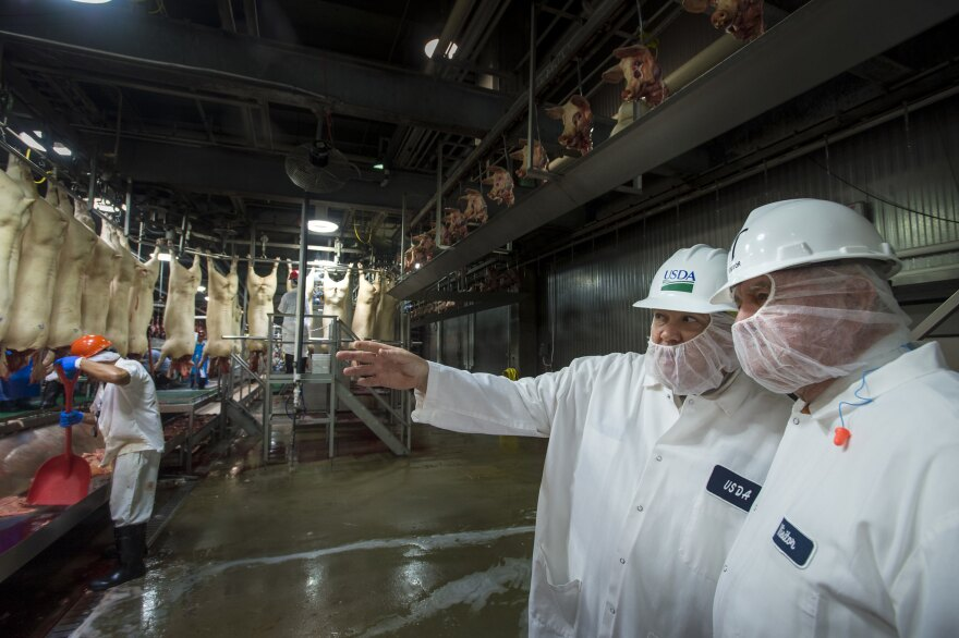 A U.S. Department of Agriculture (USDA) Inspector shows Agriculture Secretary Sonny Perdue around the processing floor of the Triumph Foods pork processing facility in April of 2017.