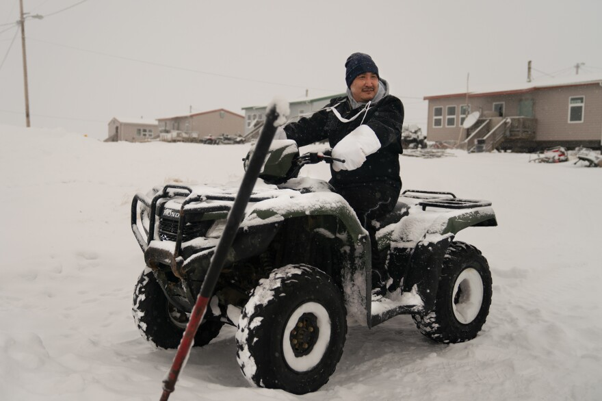Noah Lincoln, a subsistence hunter and assistant coach for the local high school boys' basketball team, sits on his ATV outside his home in Toksook Bay.