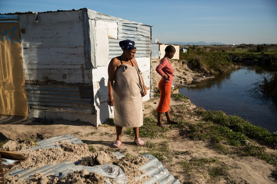 "Nomthandazo Tyikiane (in the towel) and Siphamandala Tebekwana survey the damage done by the Kuils River the night before during a storm. Tyikiane's shack was destroyed so she was sleeping at a friends. ""This place is like the wild,"" she said. On the other side of the river is a reserve owned by Cape Nature."