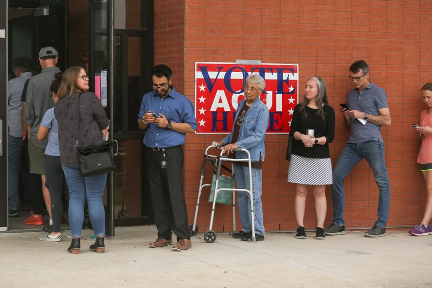 A line of voters waits to cast ballots at McCallum High School during the primary March 3.