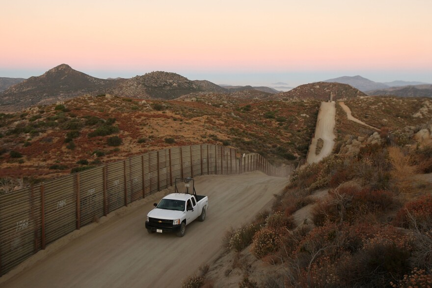 A US Border Patrol agent searches for tracks after a night of surveillance using night-vision equipment as agents carry out special operations near the US-Mexico border fence.