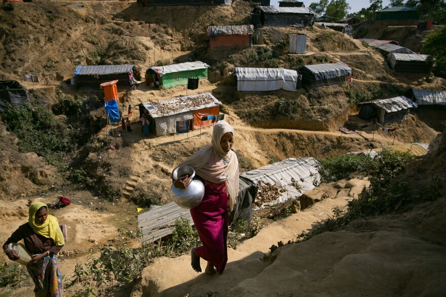 Dil Bahar, a 32-year-old Rohingya refugee (in the red dress), and a relative carry water to their shelter in the Balukhali refugee camp.