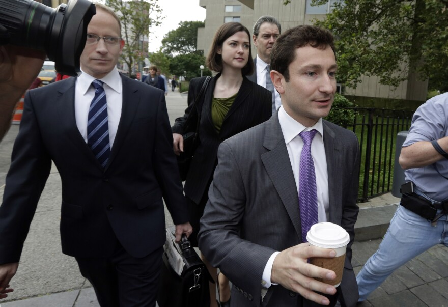 Former Goldman Sachs trader Fabrice Tourre walks to a federal court in Manhattan with his attorneys Thursday. A jury found Tourre liable in a massive securities fraud case.