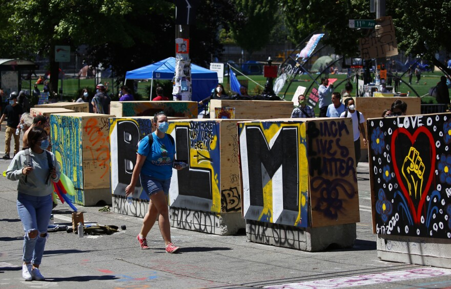 People walk around new concrete barricades topped with plywood that were installed by city workers. To the city, the new barriers open access for local traffic, but protesters believe the move shrinks their protest space.