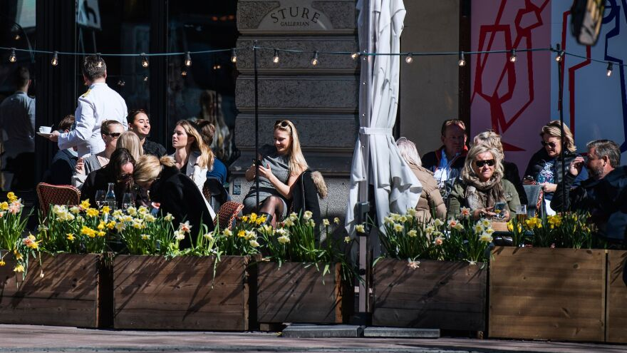 People enjoy the spring weather in mid-April at a restaurant in Stockholm during the coronavirus pandemic.