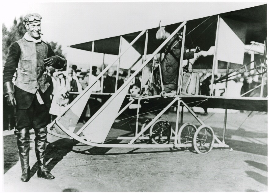 A photo of Cal Rodgers next to his airplane.