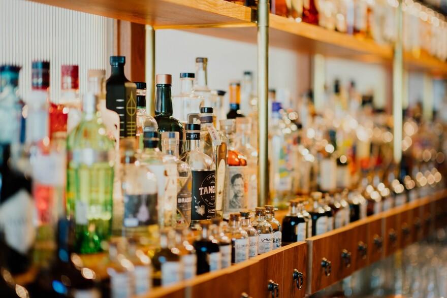 Shelves hold dozens of bottles of alcohol