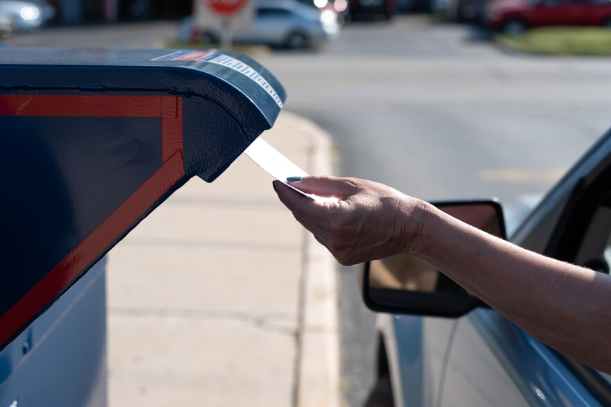 A woman pulls her car up to a mailbox and rolls down her window. In her hand is a mail-in ballot. She reaches her hand out of the car window and is about to put her ballot into the mailbox.