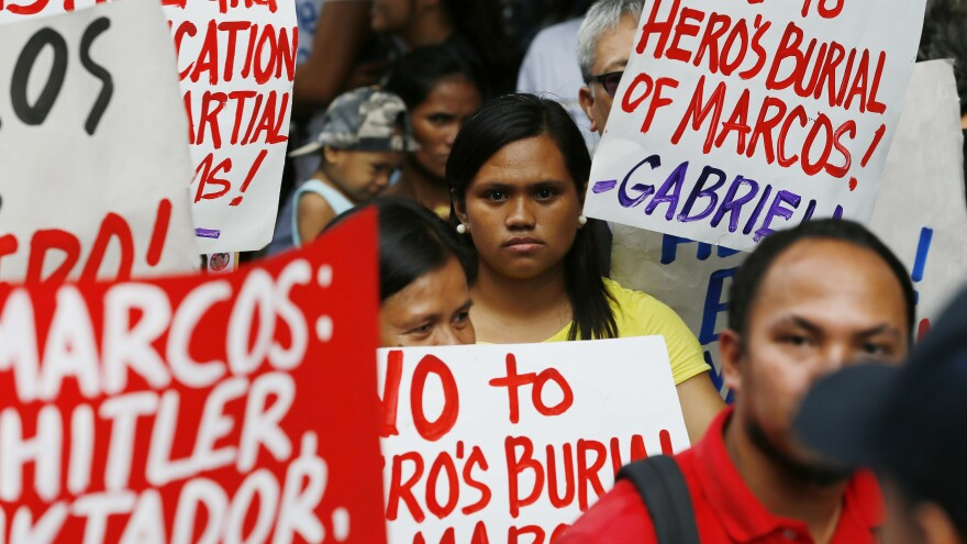 Protesters listen to the ruling of the Philippine Supreme Court allowing the body of late Philippine dictator Ferdinand Marcos to be buried at the country's Heroes' Cemetery.
