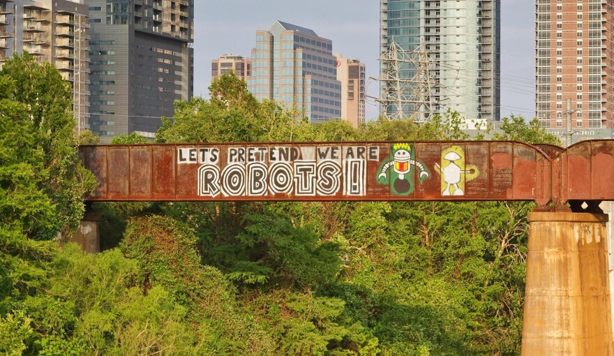 """""""Let's Pretend We Are Robots!"""" is painted on the train bridge over Lady Bird Lake."""