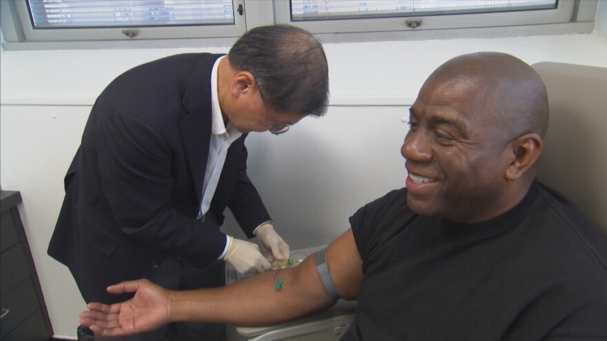 Dr. David Ho, an HIV/AIDS specialist, draws blood from Magic Johnson, one of the people featured in <em>Endgame: AIDS in Black America</em>.