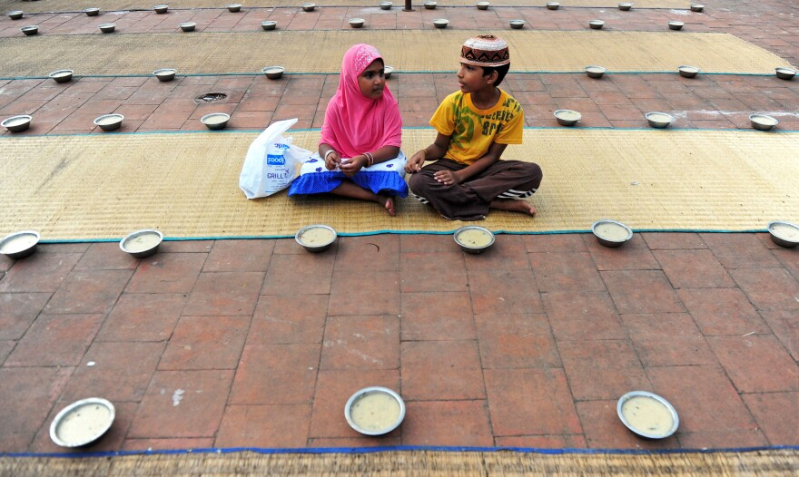 Young Indian children sit with bowls of porridge (<em>nombu kanji</em>) as they prepare to break the fast with the Iftar meal during the Islamic month of Ramadan at The Wallajah Big Mosque in Chennai last July.