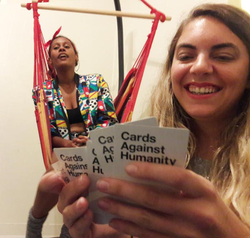 """Valerie Hill plays Cards Against Humanity in """"the social room"""" at Lunchbox Miami while Yajaira De La Espada looks on."""
