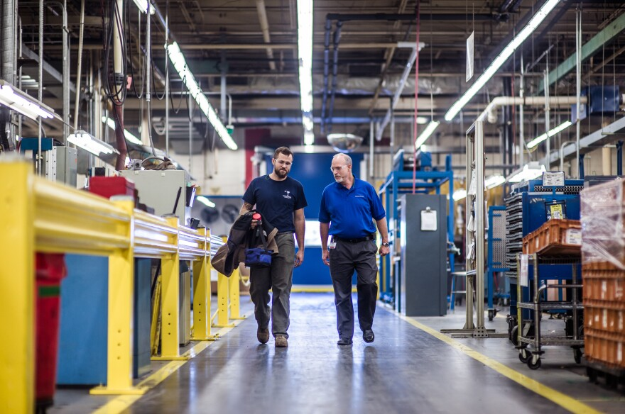 John Harris (left) walks with Warren Snead, a manager for Cooper Standard, an auto parts manufacturing factory near Spartanburg, S.C. After working as an electrician in the Air Force, Harris found the apprenticeship program at Cooper Standard, where he learns while working on the job.