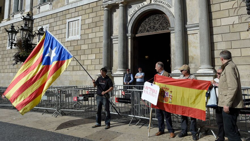 Some people unfold a Spanish flag as another man waves a Catalan pro-independence flag in front of the Catalan government headquarters in Barcelona on Monday. Spain enters uncharted and potentially perilous territory today as Madrid moves to take over the running of Catalonia, in response to the region's parliament unilaterally declaring independence.