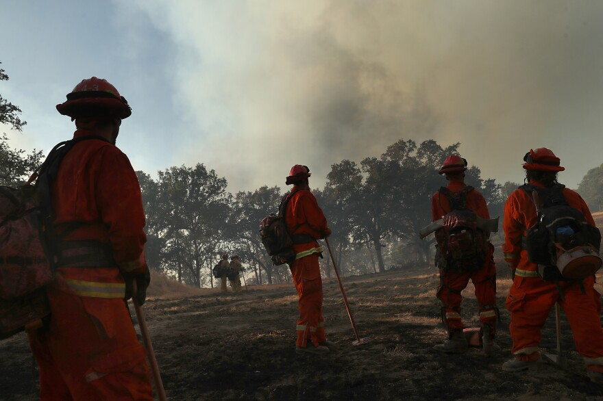 """<a href=""""https://www.npr.org/2014/07/31/336309329/thousands-of-inmates-serve-time-fighting-the-wests-forest-fires"""">Inmate firefighters</a> take a break from battling the River Fire in Lakeport, Calif., on Aug. 1."""
