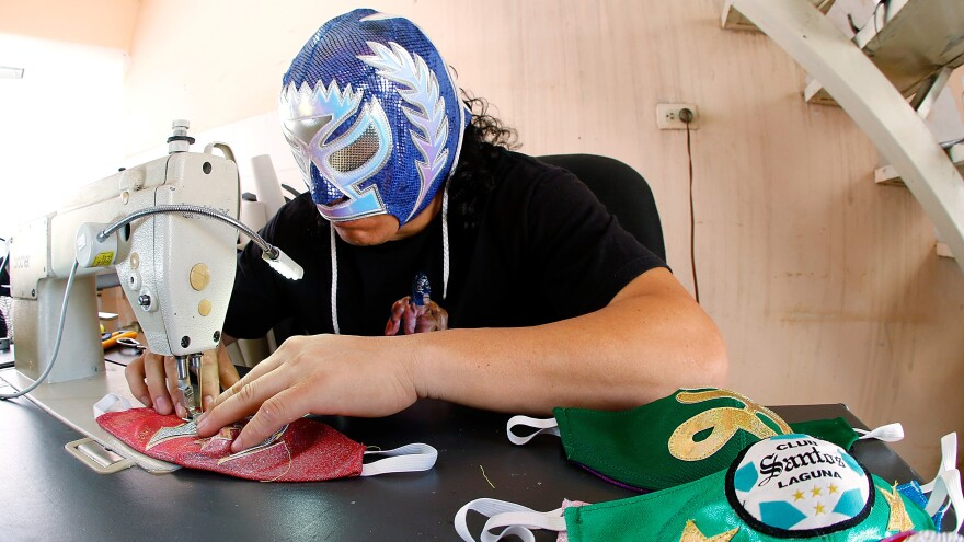 Mexican <em>lucha libre</em> wrestler Hijo del Soberano sews face masks since his matches have stopped due to the COVID-19 pandemic.