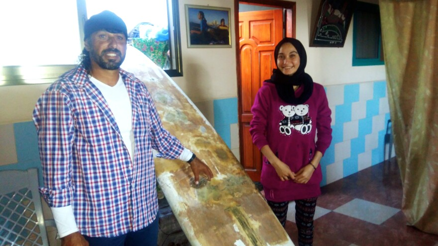 Sabah Abu Ghanim (right), began surfing at age 5 in the Mediterranean off the coast of the Gaza Strip. She was taught by her father, Rajab Abu Ghanim (left). But now that she's 17 and has graduated from high school, Sabah's parents have arranged a marriage and told her it's time to quit surfing. Here, father and daughter pose at home with a secondhand surfboard Rajab bought for the the family.