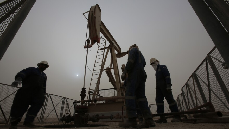 Men work on an oil pump during a sandstorm in the desert oil fields of Sakhir, Bahrain, in January.