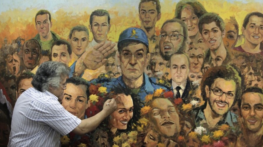 """Egyptian artist Taha el Korany finished a painting showing a military officer saluting the """"martyrs"""" of Egypt's revolution at his studio this week — a day after an Egyptian court decided to combine the trials of the former interior minister and ousted President Hosni Mubarak."""