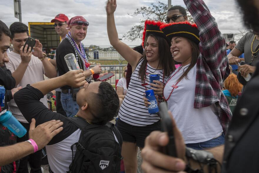A crowd of parade goers cheer as a man drinks an alcoholic beverage