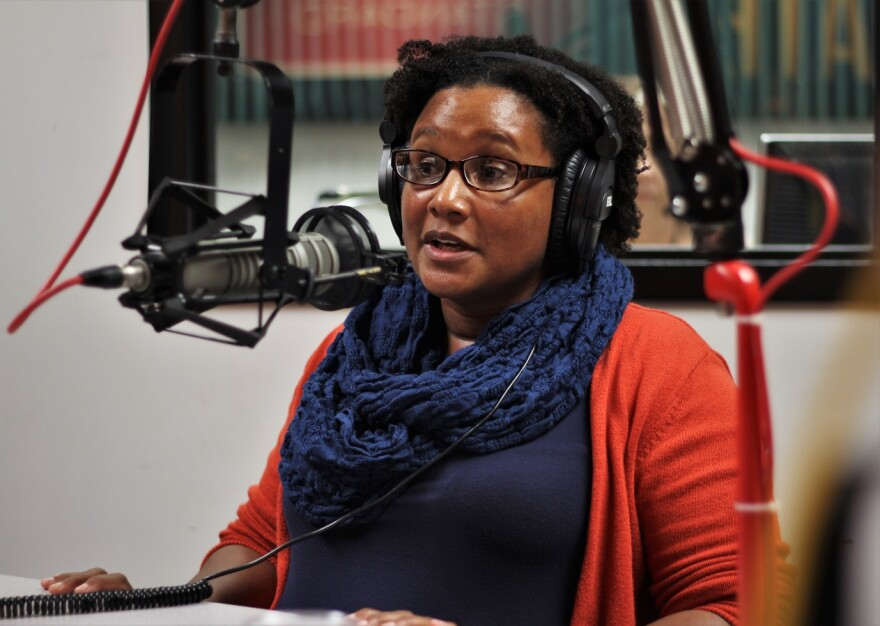 Jeanette Jones wearing headphones and seated at a microphone in the KCUR studio.