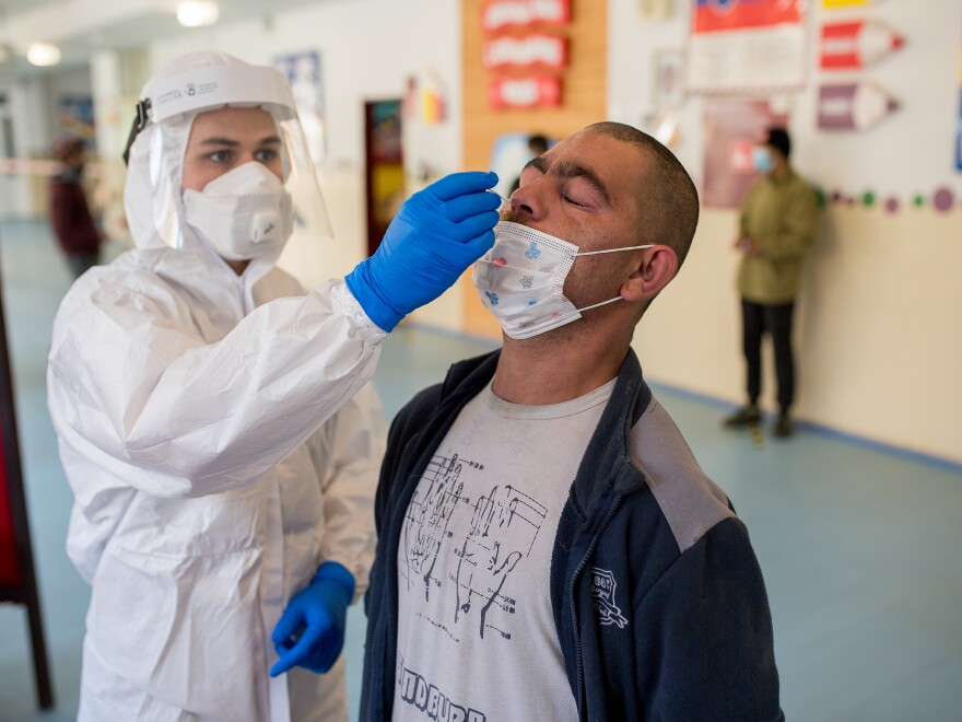 A man is tested for the coronavirus on Sunday in Košice, Slovakia, as part of a nationwide effort to test nearly everyone over age 10 for the virus.