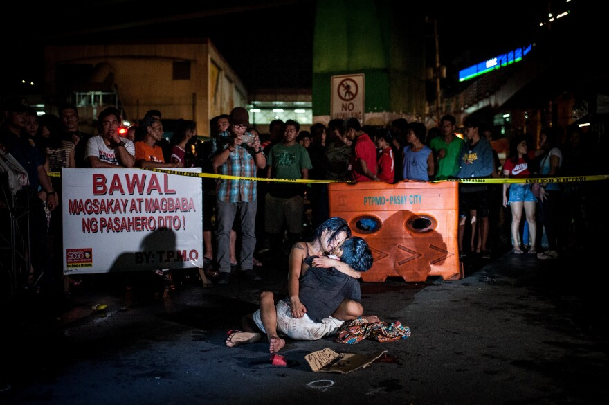 A grieving woman clutches her dead husband after armed assailants shot him in a main thoroughfare in July in Manila, Philippines. The man was accused of being a drug peddler, a claim disputed by his wife, who maintained her husband was nothing more than a pedicab driver plying his trade when he was shot in front of her.