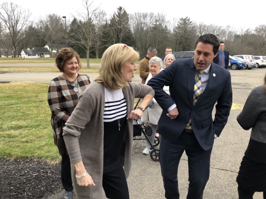 Ohio Secretary of State Frank LaRose, right, elbow bumps Michele Engelbach, left. Engelbach runs a senior living facility in Mt. Vernon, Ohio, which is no longer a voting location because of the coronavirus outbreak.