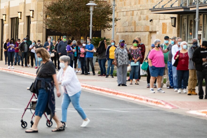 A long line of people wait to vote on the first day of early voting at the Southpark Meadows polling place in South Austin.