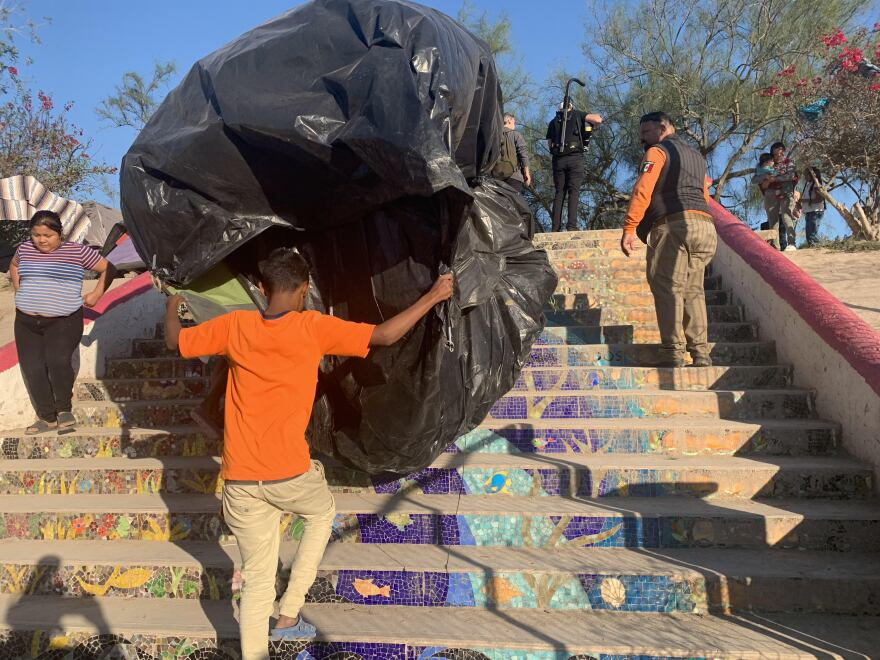 A young boy moves his tent from an encampment where he and others have stayed for months while they wait for their immigration court cases to unfold in the U.S. under the Trump administration's Remain in Mexico policy.