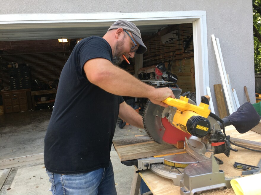 John Buhr using recycled lumber to build a playhouse for his young children.JPG