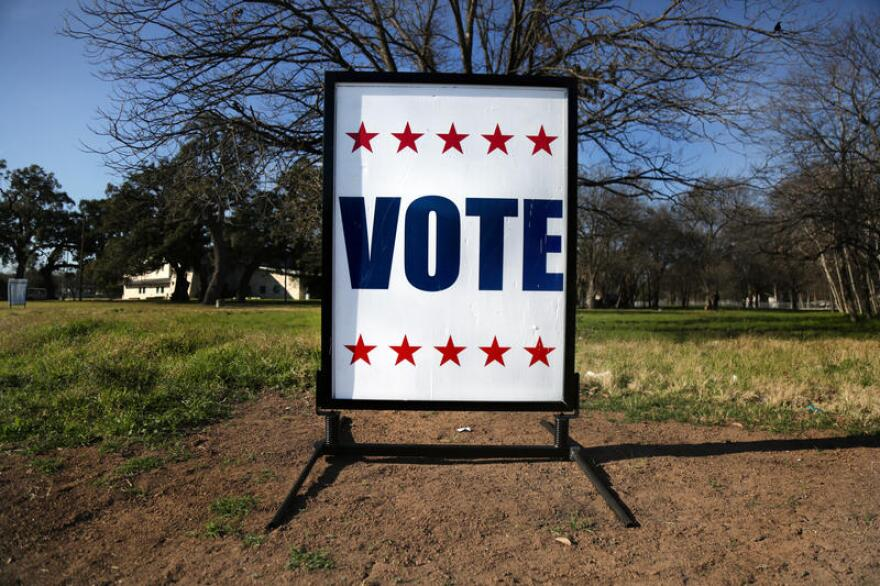 "A sign that says ""VOTE"" outside a polling place."