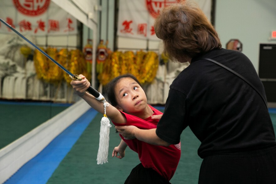 Twelve-year-old Ellen Yang practices her performance for the USAWKF National Team Trials while Zhang corrects her form.
