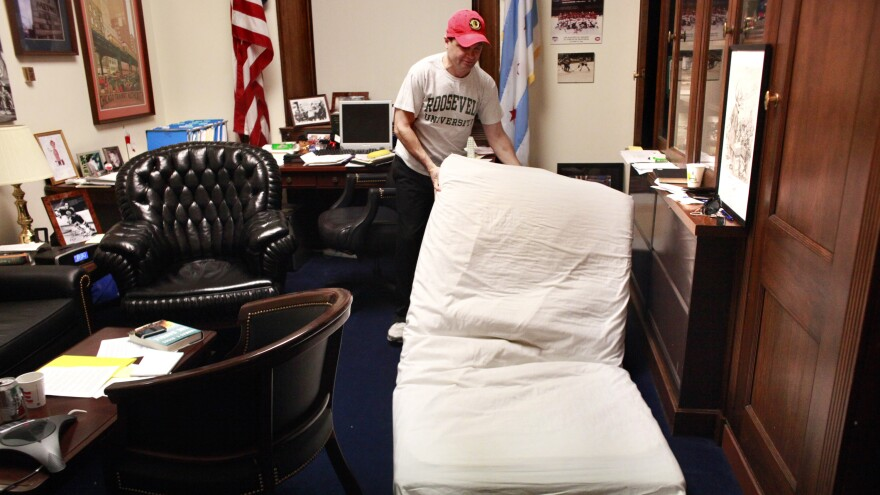 "Rep. Mike Quigley, whose Washington, D.C. office doubles as his home away from Chicago, lays his mattress onto the floor before going to sleep. While some see a political benefit, ""it's not something I'm thrilled about,"" Quigley said. ""It's just circumstances."""