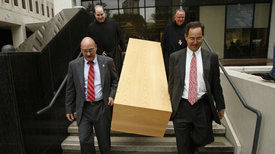 Deacon Mark Coudrain, bottom left, Rev. Charles Benoit, top left, Abbot Justin Brown, top right, and attorney Evans Schmidt carry a casket built by Benedictine monks down the steps of the U.S. federal district courthouse on Aug. 12, 2010.