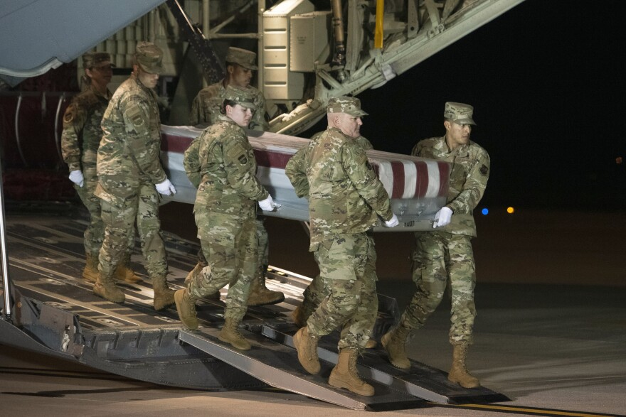 An Air Force team moves a transfer case containing the remains of one of the young sailors killed after a Saudi military student opened fire at Naval Air Station Pensacola last month. Officials are expected to soon announce that about 20 Saudi military students will be expelled from the U.S.