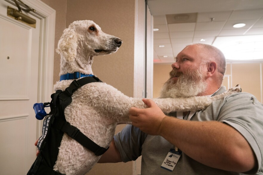 Navy veteran Thomas Gregg sits with his service dog, Gauge, at the conference.
