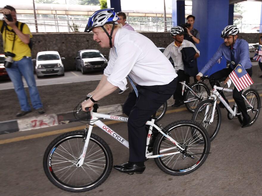 London Mayor Boris Johnson rides a bicycle on Dec. 1 during a city tour in downtown Kuala Lumpur, Malaysia.