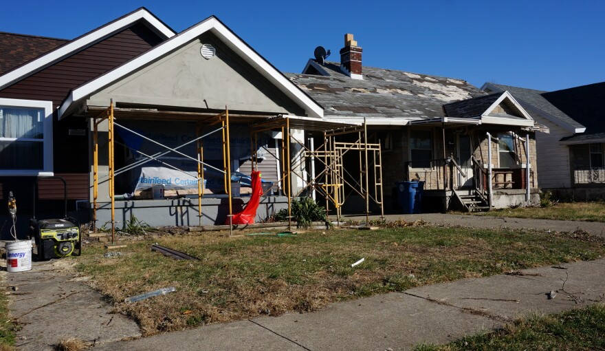 The home on the left is close to completely restored, but no repairs have been made to the damaged home on the right.