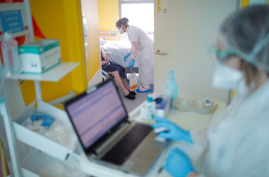 Medical workers wearing protective masks and suits treat patients at the pulmonology unit at the hospital in Vannes where patients suffering from coronavirus disease (COVID-19) are treated.