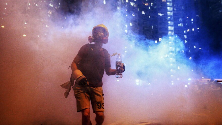 A protester stands in the midst of tear gas during a confrontation with police in Hong Kong during the early hours of Sunday local time.