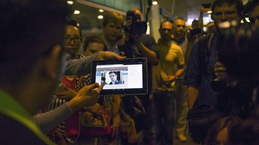 Journalists show passengers arriving at Russia's Sheremetyevo airport on Sunday an image of Edward Snowden.