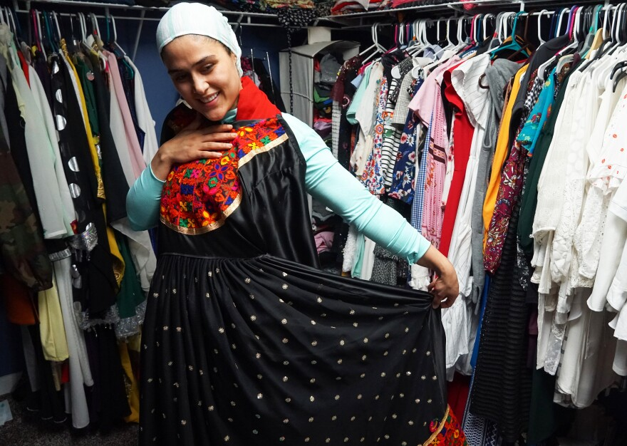 Mojda Sidiqi models one of her designs, a long black silk dress with an embroidered brocade bib on April 10, 2019.