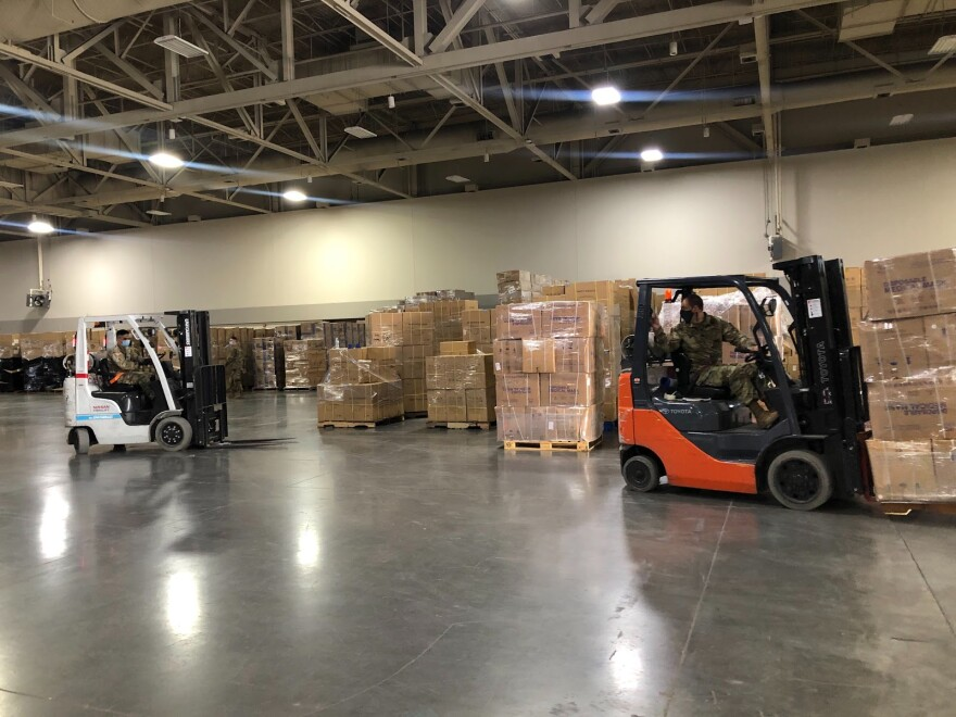 Photo of two forklifts in a large warehouse full of cardboard boxes.